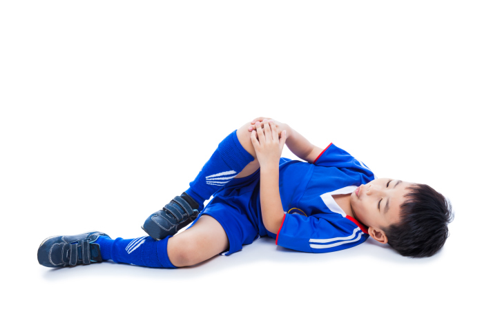 Sports injury. Youth asian (thai) soccer player in blue uniform with pain in knee. Isolated on white background. Studio shot. Full body. Boy lie down.